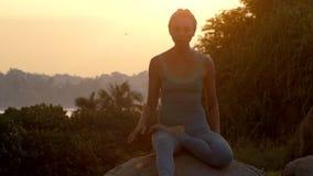年轻女人实践在大岩石慢动作的瑜伽asanas 股票视频