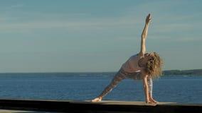 年轻女人实践的瑜伽户外在夏天 r 股票视频