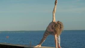 年轻女人实践的瑜伽户外在夏天 r 股票录像