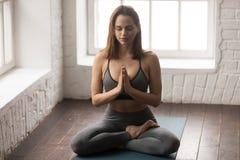 年轻女人实践的瑜伽,坐在莲花姿势,Padmasana锻炼 免版税库存照片