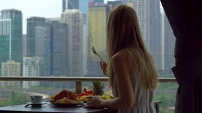 年轻女人家庭女教师食用与一个男孩的早餐俯视市中心的摩天大楼的阳台的 影视素材