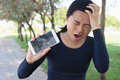 年轻女人尖叫在与一个残破的智能手机的愤怒 免版税库存照片