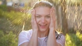 年轻女人微笑和笑在雨下 雨下降在她的面孔的秋天,并且她对生活和自然满意 股票视频