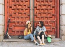 _年轻女人快乐夫妇看和微笑彼此在红色门背景 同性幸福和快乐的概念 免版税库存图片