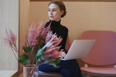 年轻女人或工作和写使用膝上型计算机的大学生在膝盖 坐在咖啡馆在窗口附近,浪漫心情,温暖的颜色 库存图片