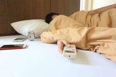 年轻女人手举行遥远的空调和在家睡觉在卧室 免版税库存照片