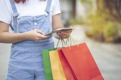 年轻女人手藏品片剂巧妙的设备和购物带来有身分的在汽车停车场 免版税库存照片
