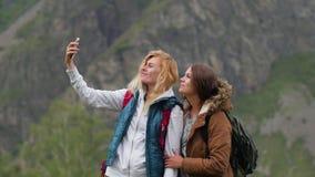 年轻女人拍在电话的照片反对山的背景 在山的移动通信 股票录像