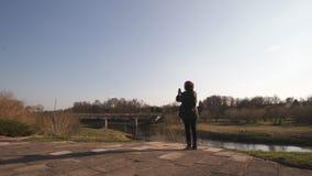 年轻女人拍照片使用河她的电话应用程序有一座桥梁的在背景中在波罗的海国家市萨比莱 股票录像
