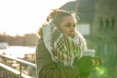 年轻女人拿着一个咖啡杯温暖她的手 库存图片