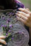 年轻女人拿着一个草帽和淡紫色开花的淡紫色花束  紫罗兰色心情 免版税库存照片