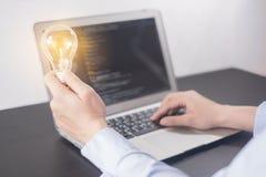 年轻女人拿着电灯泡,妇女手的程序员手编码和编程在屏幕膝上型计算机,与创新的新的想法 免版税库存图片