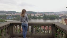 年轻女人敬佩从阳台的城市视图小山的,照相机从后面移动 影视素材