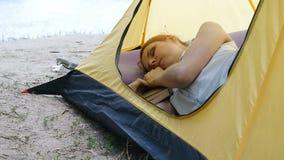 年轻女人旅客在帐篷睡觉 疲倦的徒步旅行者女孩睡着了与在一个野营的帐篷的一本书 远足,旅行,绿色 股票录像