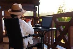 年轻女人旅客坐在与膝上型计算机和饮用的茶的大阳台 免版税库存照片
