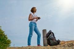 年轻女人旅行与背包并且决定拍有些照片在一个美好的地方 与太阳的天空在backround 库存照片