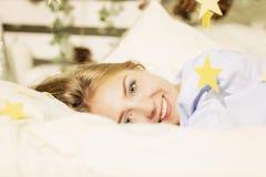 年轻女人早晨在床上在新年的内部 免版税库存图片