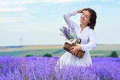 年轻女人是在淡紫色花田,美好的夏天风景 图库摄影