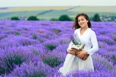 年轻女人是在淡紫色花田,美好的夏天风景 免版税库存图片