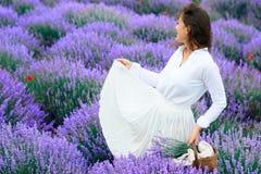 年轻女人是在淡紫色花田,美好的夏天风景 库存图片
