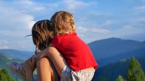 年轻女人显示她的女儿山 妈妈和运载她的肩膀的一个女儿沿山蛇纹石 股票视频