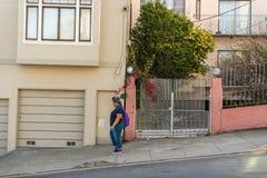 年轻女人步行沿着向下一个Lombardt街倾斜在旧金山,加利福尼亚,美国 库存照片