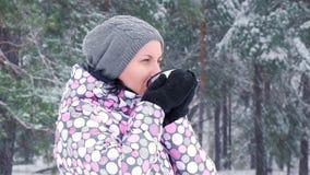 年轻女人游人在多雪的森林和饮用的热的茶休息 室外休闲,旅游业的概念 股票录像