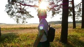 年轻女人游人通过森林走通过树 女孩旅行与背包在日落 a的概念 股票录像