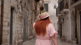 年轻女人游人通过老城市街道走在意大利,背面图 股票视频