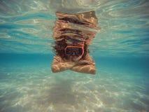 年轻女人游泳和潜航与面具和飞翅在清楚的大海 免版税库存照片