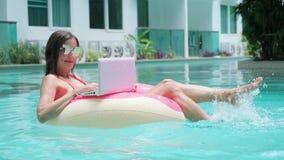 年轻女人游泳在一个游泳的圈子的海 女孩休息在一个可膨胀的圈子的水池的与计算机,上面 股票视频