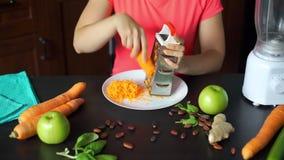 年轻女人滤栅新鲜的红萝卜在厨房里 股票视频