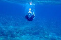 年轻女人潜航的海里的照片 在水下的废气管下潜在鱼学校 正面潜航的面具的妇女 库存图片