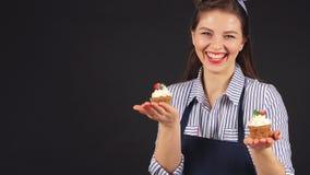 年轻女人用杯形蛋糕在手中微笑对照相机的点心师 股票录像