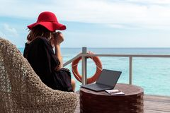 年轻女人用红色帽子饮用的咖啡和研究在一个热带目的地的一台计算机 库存图片