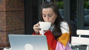 年轻女人用途膝上型计算机和饮料咖啡 股票录像