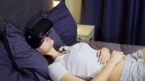 年轻女人用途虚拟现实,说谎在床上的枕头的手表VR录影顶视图  股票视频