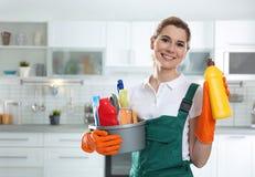 年轻女人画象有洗涤剂水池和瓶的在厨房里 库存图片