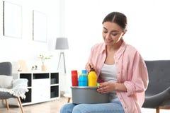 年轻女人画象有洗涤剂水池的在客厅 库存照片