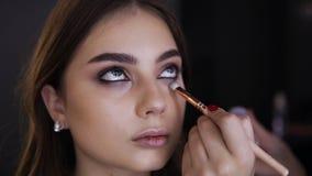 年轻女人画象,当构成眼睛在化妆演播室时 使用应用的刷子的化妆师在低落的明亮的眼影膏 股票视频