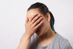 年轻女人的演播室画象,她投入她的手对她的面孔在羞辱和失望 失败和facepalm的概念 免版税库存图片