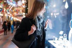 年轻女人的照片边商店窗口的在晚上 免版税库存照片