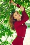 年轻女人的美好的笑容一件红色礼服的 E 图库摄影