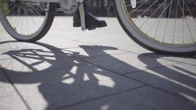 年轻女人的脚骑她的在城市关闭的黑起动的自行车  城市居民的休闲 活动家 股票视频