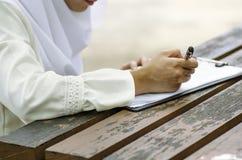 年轻女人签署的形式,坐木桌 免版税库存照片