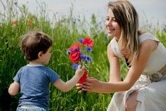 年轻女人给小孩男孩矢车菊花束  免版税库存照片