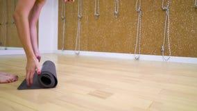 年轻女人脚和手看法展开席子的在健身演播室 股票录像
