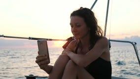 年轻女人航行游艇并且使用智能手机-采取selfie在日落 影视素材