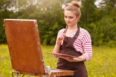 年轻女人艺术家使用写生簿,享受美好的自然和工作的女孩的绘画图片水平的射击被启发  库存照片
