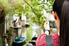 年轻女人获得乐趣在地方运河城市在有照相机的中国在做图片的智能手机 免版税库存图片